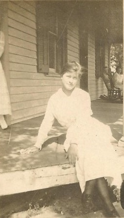 She's unidentified but striking a casual pose as she sits on the edge of a porch. Why do I think it's a farmhouse? The edge of the long skirt at the left and the rocking chair in use at the other end of the deck suggest a Sunday afternoon in pleasant weather.